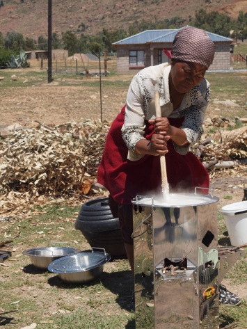 A woman cooking pap, the traditional maize porridge, for local school children.